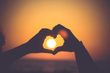 hand heart over sun